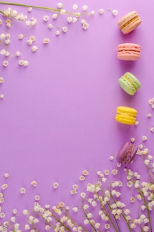 Colorful macaroons decorated with blooming lily of the valley on purple background. sweet french dessert concept. frame composition. flat lay. copyspace. vertical. greeting card concept