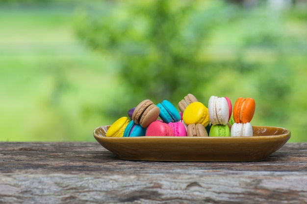 Colorful macaroons in dish on wooden table