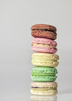 Colorful macaroons on each other on a table against a white background