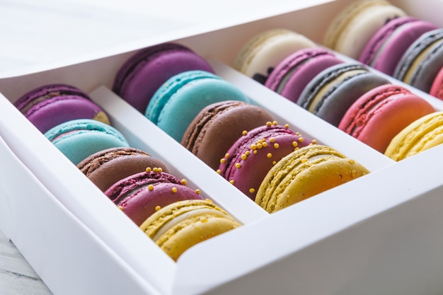 Colorful macaroons in a gift box on white table.