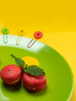 Colorful macaroons on a green plate. concept for the holiday. copy space