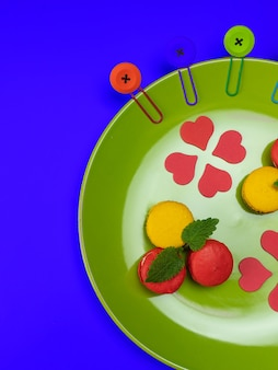 Colorful macaroons on a green plate. concept for the holiday. top view. copy space