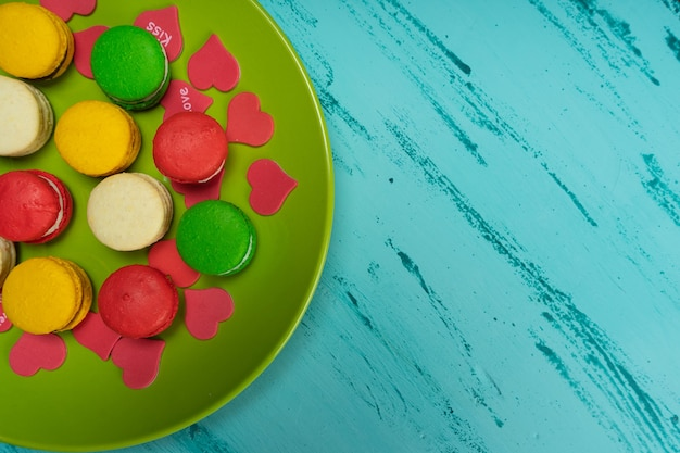 Colorful macaroons on green plate on wooden table. copy space.