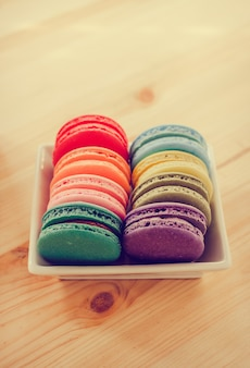 Colorful macaroons and green tea on wooden table