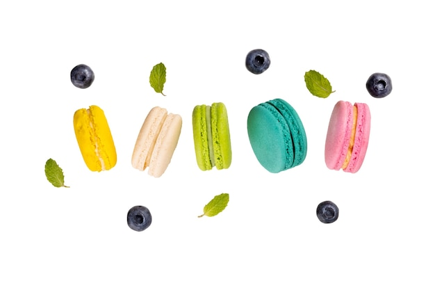 Colorful macaroons  levitating on white background with blueberries and mint leaves.
