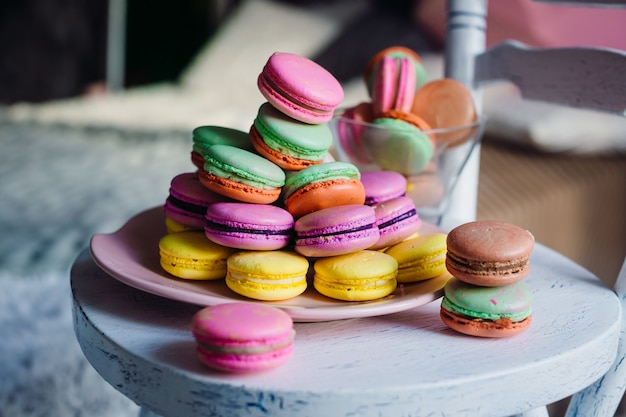 Colorful macaroons lie on pink plate