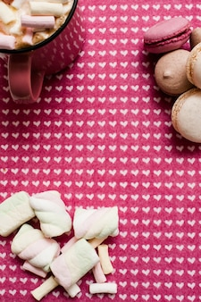 Colorful macaroons and marshmallow hot coffee drink with zephyrs love of desserts and sweets concept