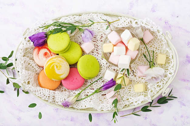 Colorful macaroons and marshmallows on a ligth background