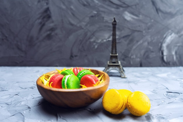 Colorful macaroons on stone table. sweet macaroons in wooden dish. copy space