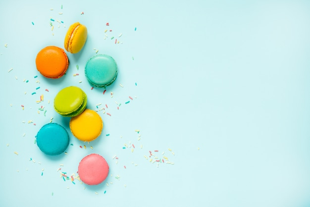 Colorful macaroons and sugar sprinkles arranged over blue