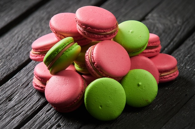 Colorful macaroons and tulips on a old wooden background.