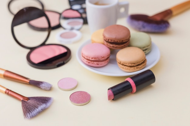 Colorful macaroons with cosmetics product on beige background