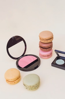 Colorful macaroons with pink blusher on beige background