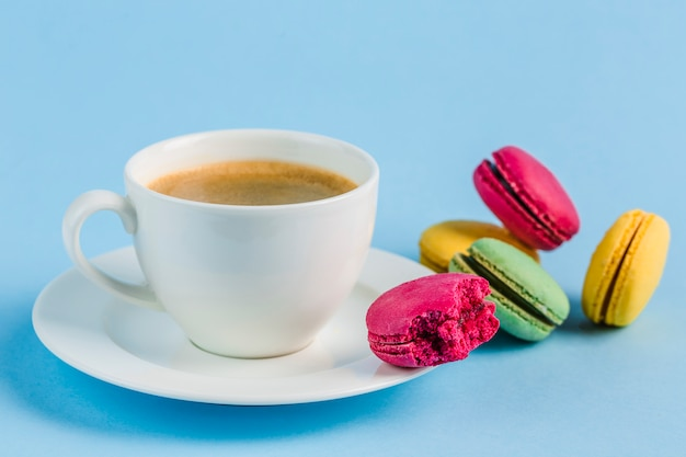 Colorful macaroons with a white cup of coffee on a blue copyspace, close-up, flatley with copyspace