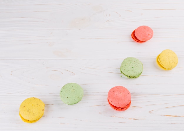 Colorful macaroons on wooden textured backdrop