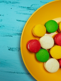 Colorful macaroons on yellow plate on wooden table. copy space.