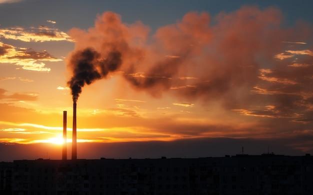 カラフルな魔法の夕日。日の出時の都市住宅の屋根。空を飛んでいる鳥。火力発電所のパイプから出る暗い煙。