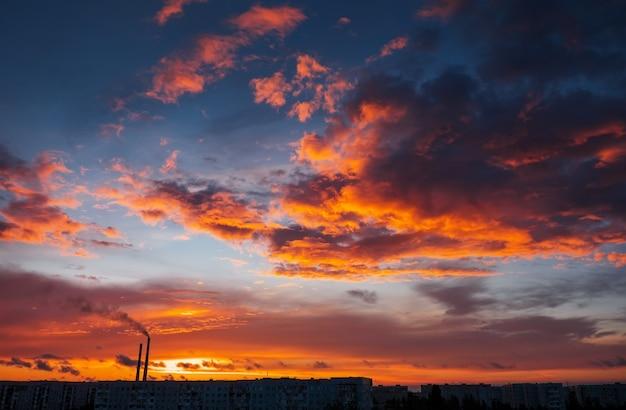 Красочный волшебный закат. крыши городских домов во время восхода солнца. птицы летают в небе. темный дым идет из трубы тэц.