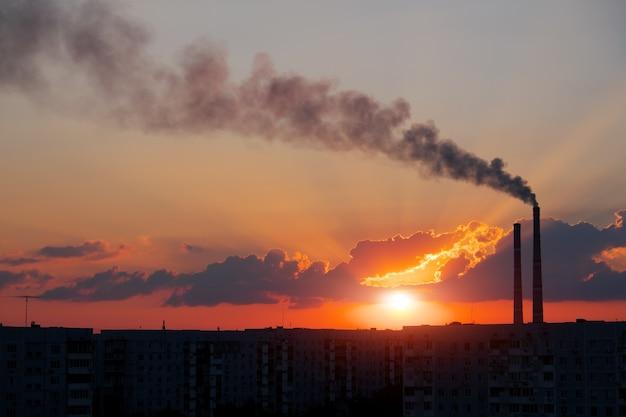 カラフルな魔法の夕日。日の出時の都市住宅の屋根。火力発電所のパイプから出る暗い煙。