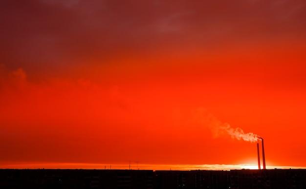 Красочный волшебный закат. крыши городских домов во время восхода солнца. темный дым идет из трубы тэц.