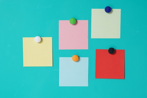 Colorful magnet sticky notes on refrigerator door background