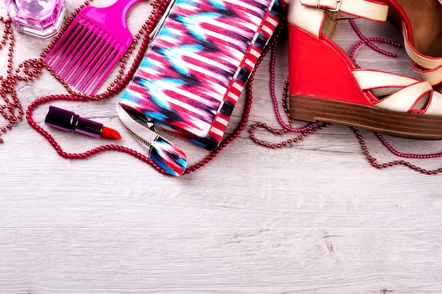 Colorful make-up bag and sandals. accessory on wooden background. creating of an elegant look. preparing for a party.