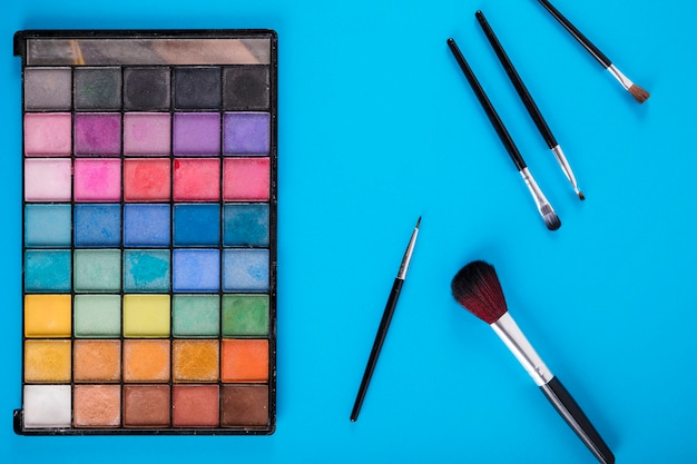 Colorful makeup palette with brushes on blue background