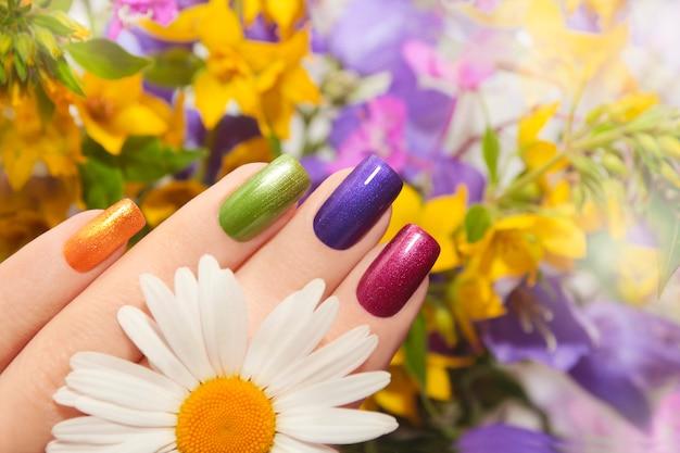 花とカラフルな手入れの行き届いた爪の正方形の形