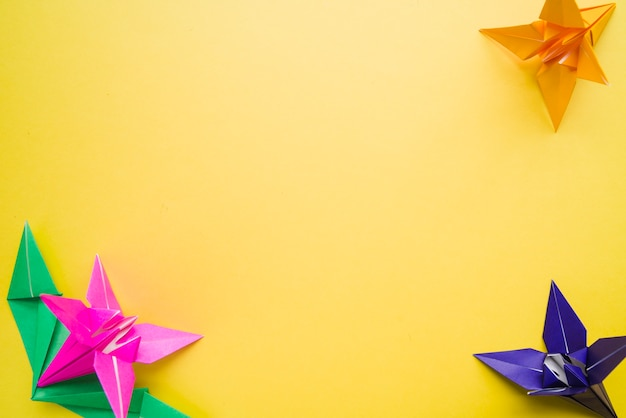 Colorful many origami paper flowers on yellow background