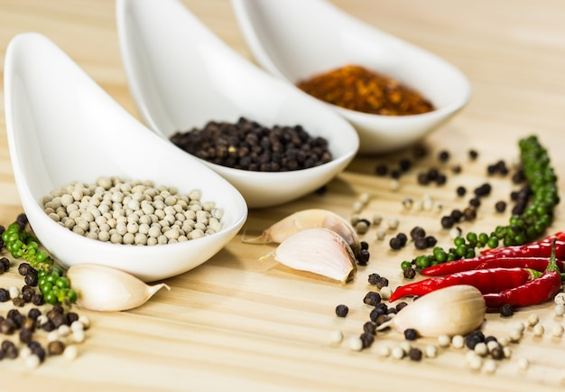 Colorful of many spices and herbs on white little bowl and spoons put on wood plank