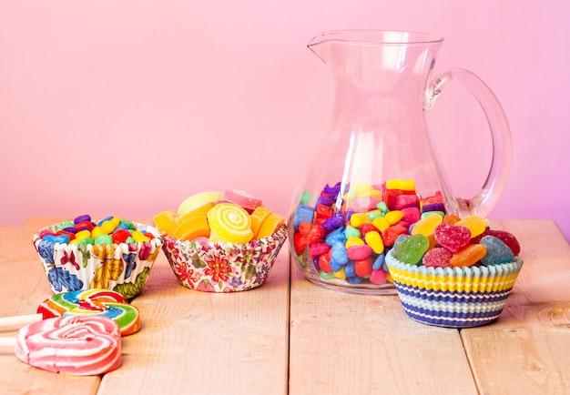 カラフルな多くの甘いゼリー、フレーバーフルーツ、ピンクのパステル背景のハート型のキャンディデザートの誕生日