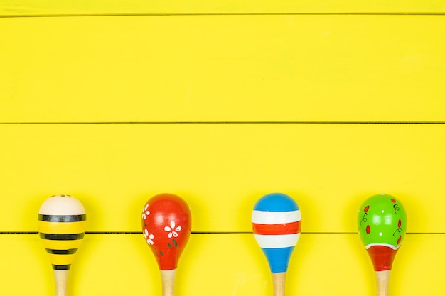 Colorful maracas  on yellow wooden board.