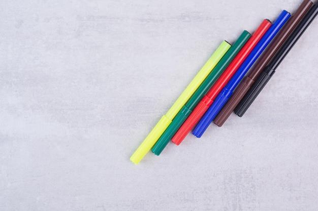 白いテーブルに設定されたカラフルなマーカーペン。