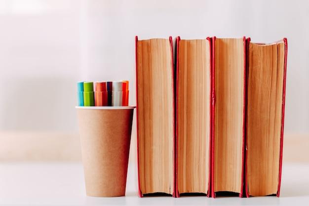 Красочные фломастеры в банке из крафт-бумаги на белом столе. школьные принадлежности. большие красные книги на столе.