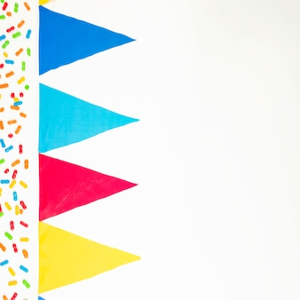 Colorful marmalade candies and bunting flag on white background
