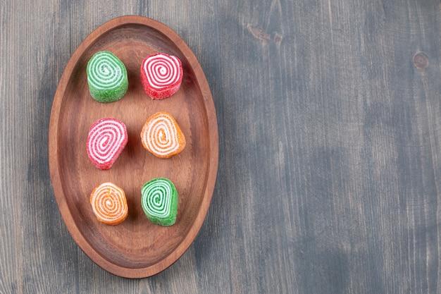 Caramelle colorate alla marmellata su piatto di legno