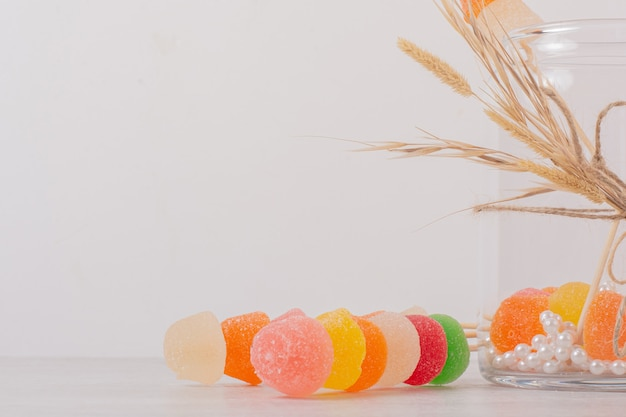 Colorful marmalades and glass jar on white.