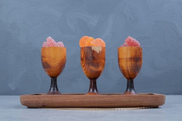 Marmellate colorate in tazze di legno sul piatto di legno. foto di alta qualità