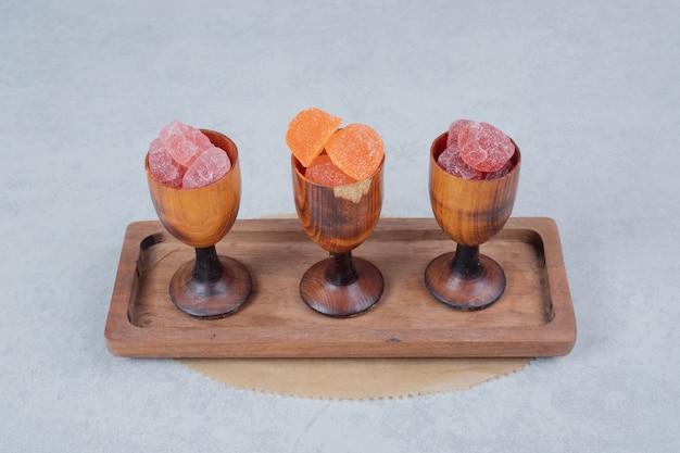 Colorful marmalades in wooden cups on wooden plate. high quality photo