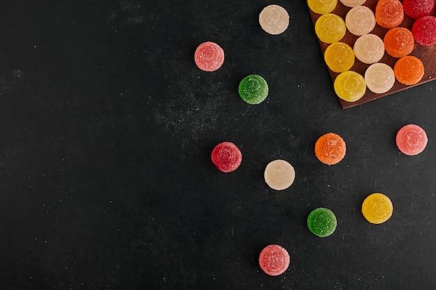 Marmellate colorate nell'angolo in alto sulla superficie nera.