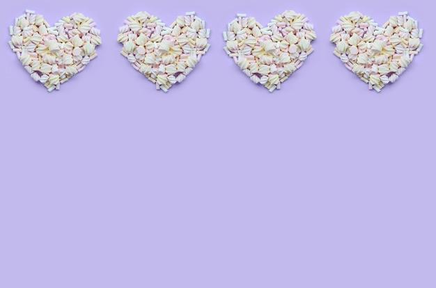 カラフルなマシュマロは紫とピンクの紙の背景にレイアウトしました。