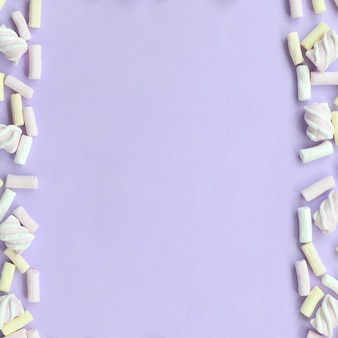 Colorful marshmallow laid out on violet paper background