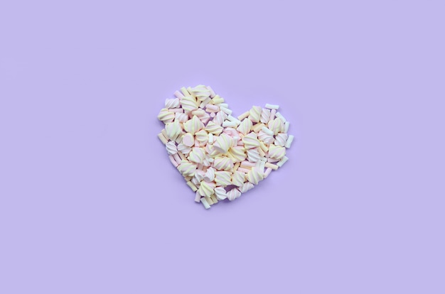 Colorful marshmallow laid out on violet and pink paper background