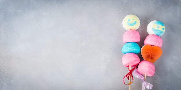 Colorful marshmallows cake pops on wooden sticks with smiling faces together.