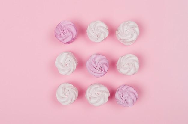 ピンクのテーブルにカラフルなマシュマロ。甘い自家製ゼファーまたはマシュマロを着色します。フラット横たわっていた。