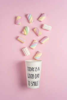 Colorful marshmallows with paper cup on pink background
