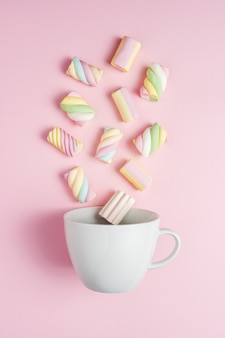 Colorful marshmallows with white cup on pink surface