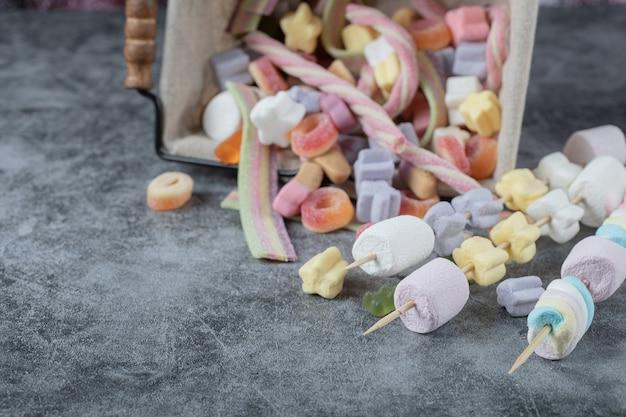 Marshmallow colorati sui bastoncini di legno per grigliare.