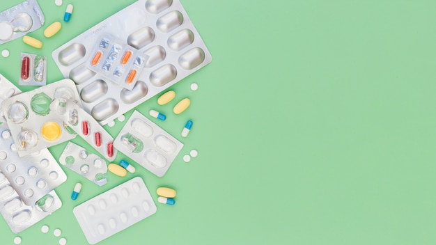 Colorful medical pills and sliver blister packs on green background