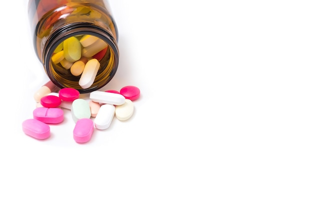 Colorful medicines and drugs in a bottle on a white background.